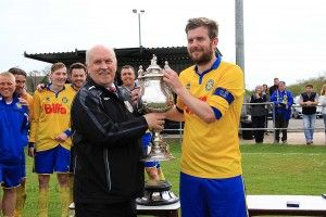 Captain Stav Roberts receives the Trophy form League Chairman Peter Maguire.