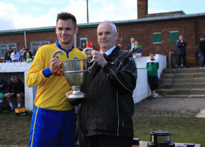 Captain Adam Nicholson receives the Wearside League Cup from League Secretary Kevin Harrison.