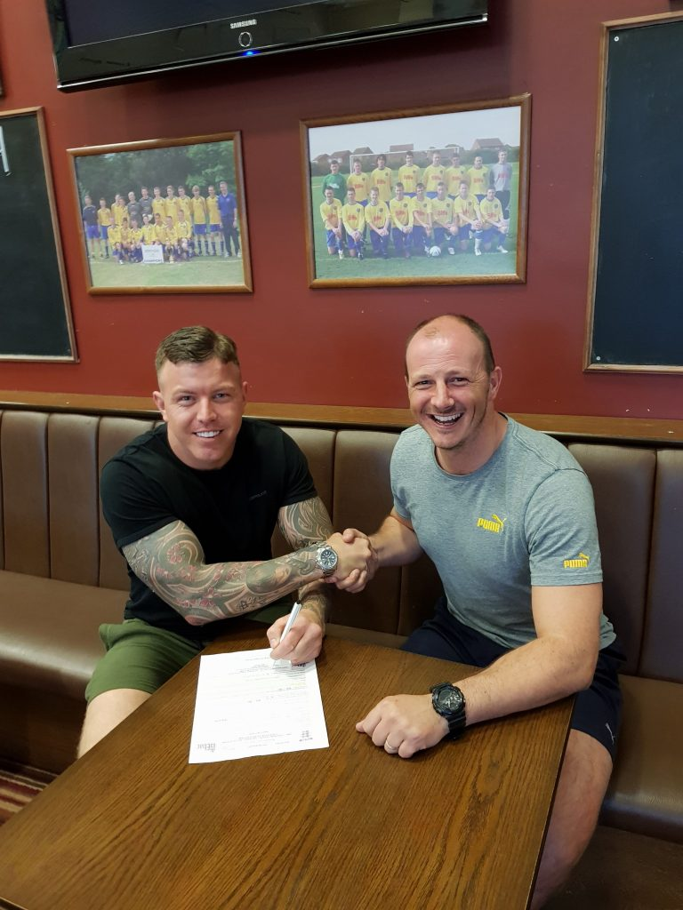 Jamie Owens signing his registration form with 1st Team Manager Michael Dunwell