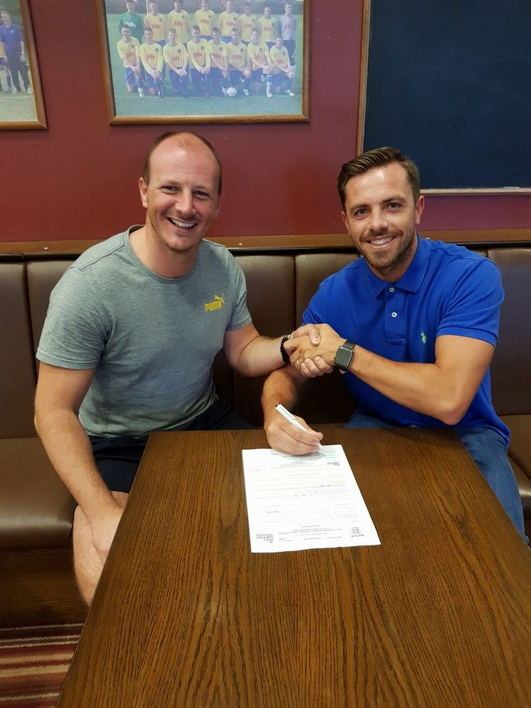 Nathan putting pen to paper with Manager Michael Dunwell.